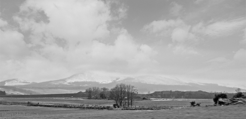 Landscape in B+W of Bennachie range of peaks covered in snow