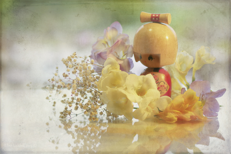 Kokeshi doll surrounded by flowers